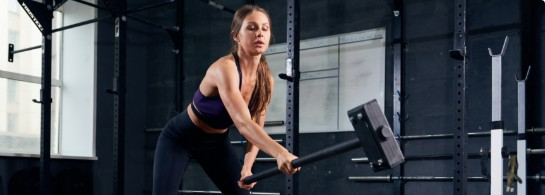 a woman in crossfit workout with hammer at P3 Training institute